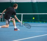 the-young-man-in-a-closed-tennis-court-with-ball