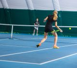the-young-girl-in-a-closed-tennis-court-with-ball